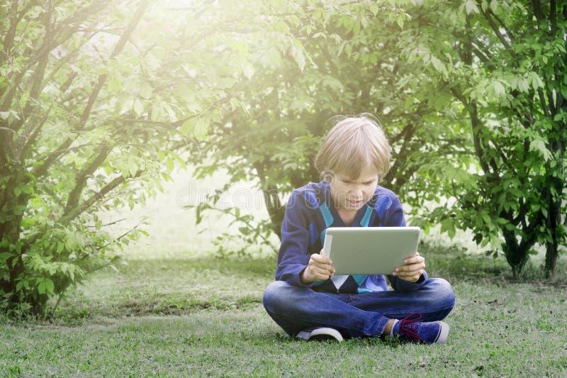 O assento de assento do menino na grama no parque com tablet pc Tecnologia, estilo de vida, educação, conceito dos povos fotos de stock