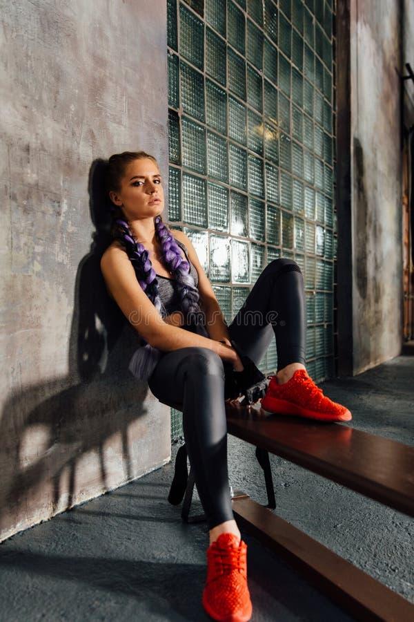 O assento de relaxamento da menina da aptidão em esportes educa o banco após um treinamento duro do encaixotamento fotografia de stock royalty free
