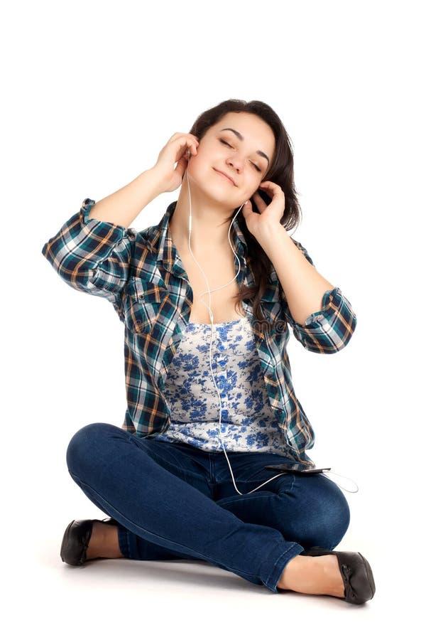 O assento louro do adolescente e escuta música fotos de stock royalty free