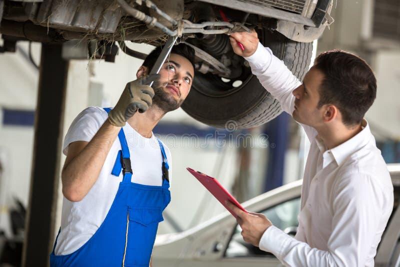 O assessor e o homem do reparo examinam o carro foto de stock