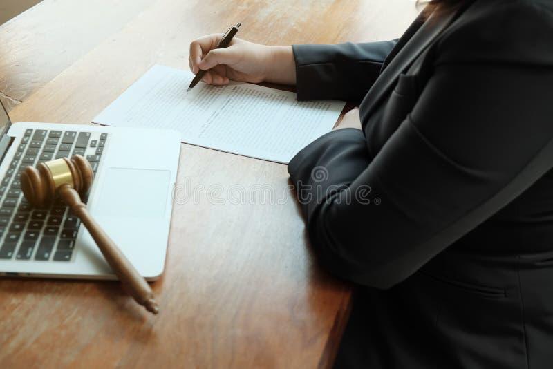 O assessor legal apresenta ao cliente um contrato assinado com martelo e lei legal foto de stock royalty free