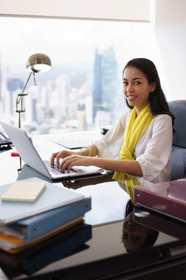 O assistente da mulher de negócio sorri na câmera que datilografa no PC imagem de stock