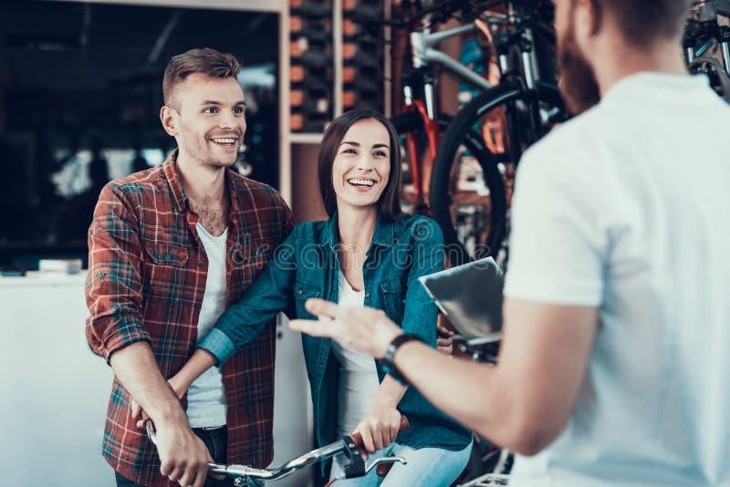 O assistente de loja ajuda pares novos na loja da bicicleta fotos de stock royalty free