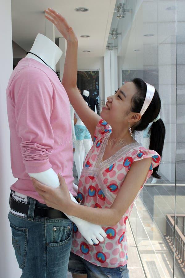O assistente de loja ajusta um mannequin fotos de stock royalty free