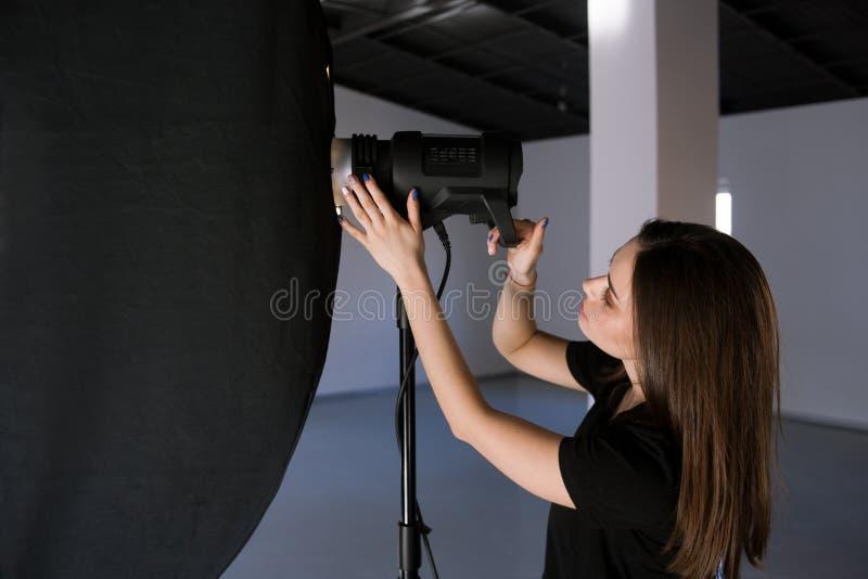 O assistente do fotógrafo ajusta a luz no estúdio fotografia de stock