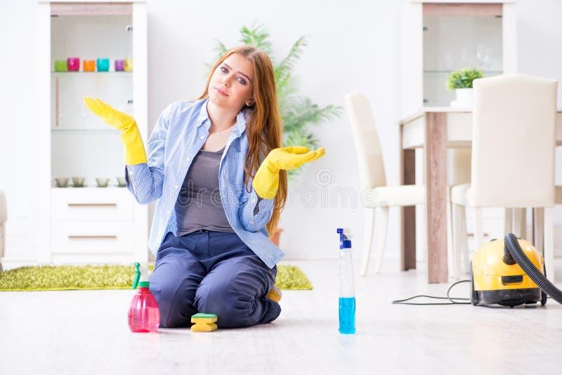 O assoalho da limpeza da jovem mulher em casa que faz tarefas imagem de stock royalty free