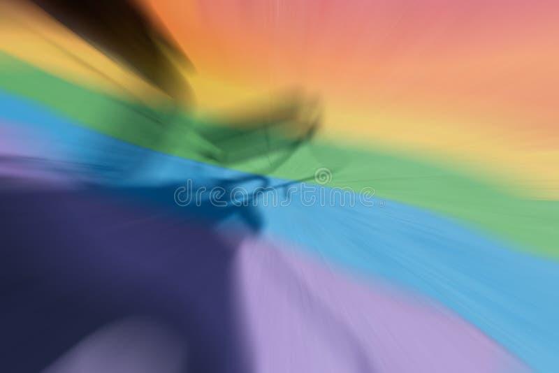 O assoalho de borracha do arco-íris colorido em um parque de diversões exterior com uma sombra forte de um assento de jogo casted foto de stock