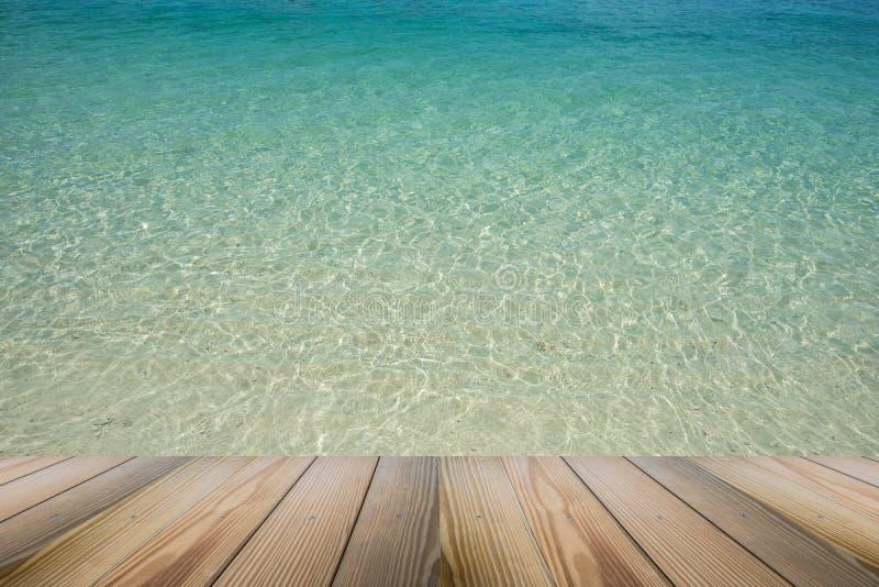 O assoalho de madeira com ideia do cenário do fundo claro cystal bonito do mar fotografia de stock