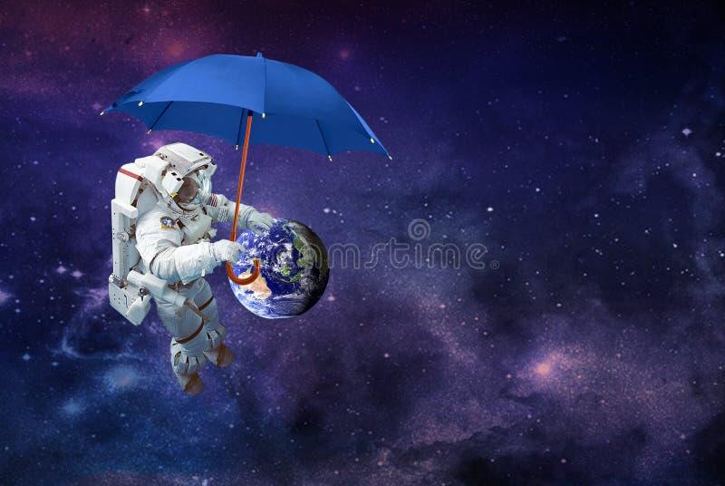 O astronauta fecha a terra do planeta dos eventos do tempo adverso com um guarda-chuva foto de stock royalty free