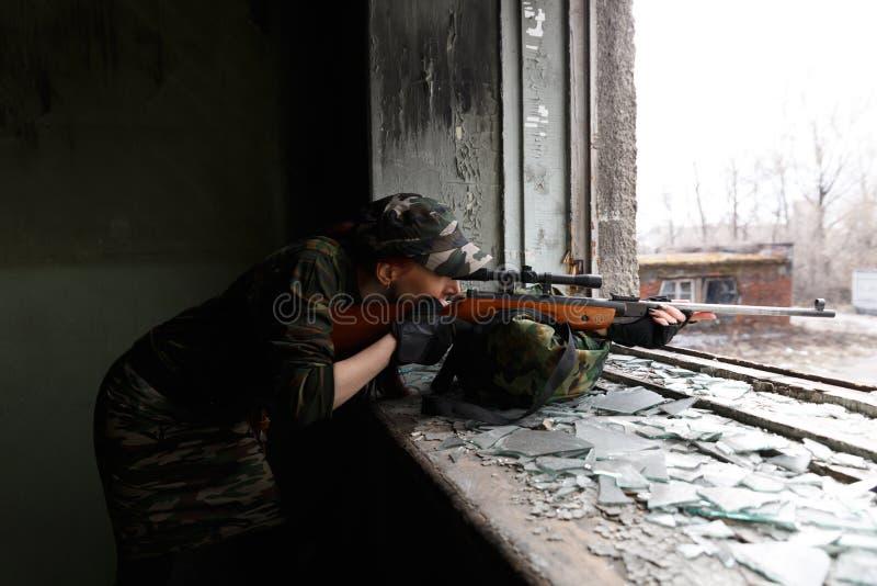 O atirador furtivo da menina olha com o espa?o O guerreiro da menina dirige seu rifle atrav?s da janela quebrada de uma constru?? imagem de stock