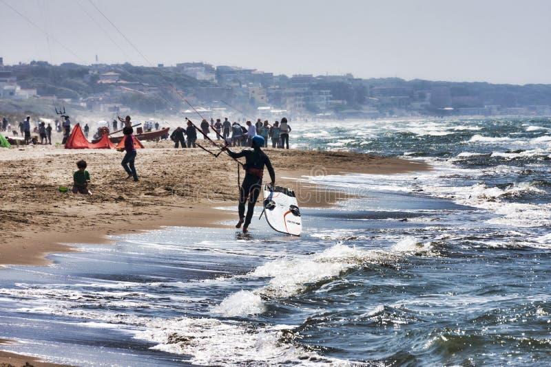 O atleta anda entre a espuma da costa das ondas com sua placa surfando do papagaio na praia romana aglomerada por banhistas e por foto de stock royalty free