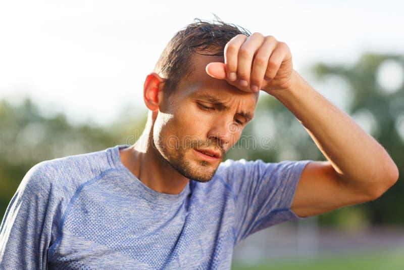O atleta cansado que limpa com a mão suou do close up da testa foto de stock