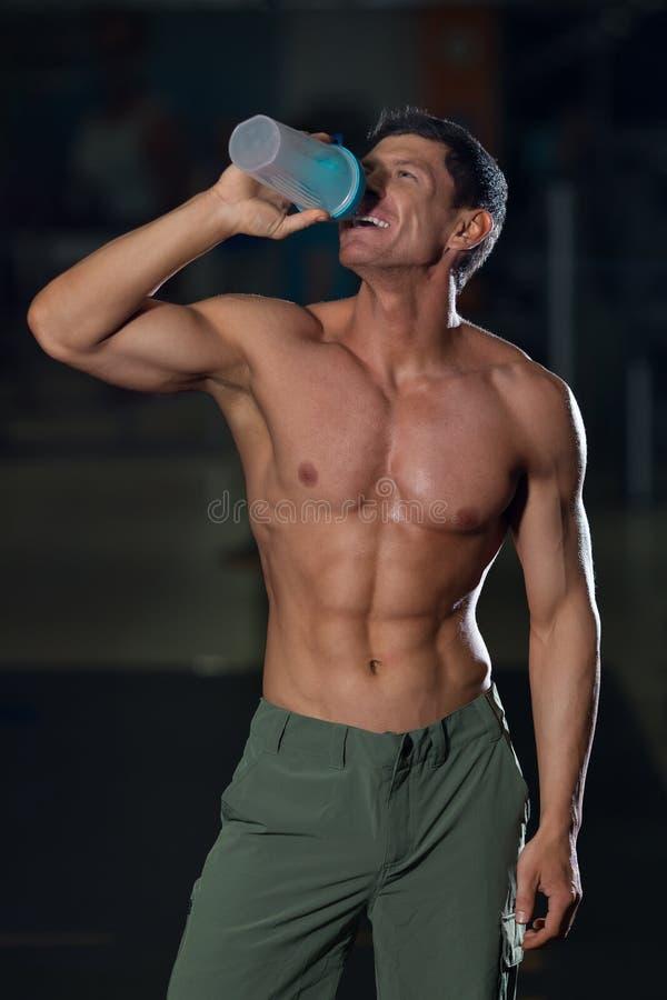 O atleta com corpo muscular bebe a água imagens de stock royalty free