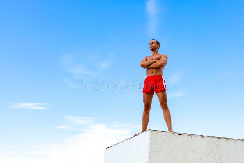 O atleta considerável Shirtless Young Man está em uma rocha contra o céu foto de stock