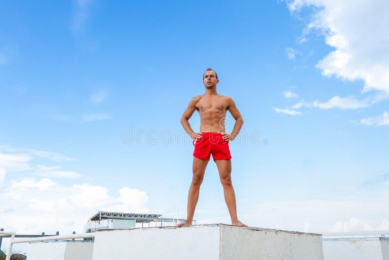 O atleta considerável Shirtless Young Man está em uma rocha contra o céu imagens de stock royalty free