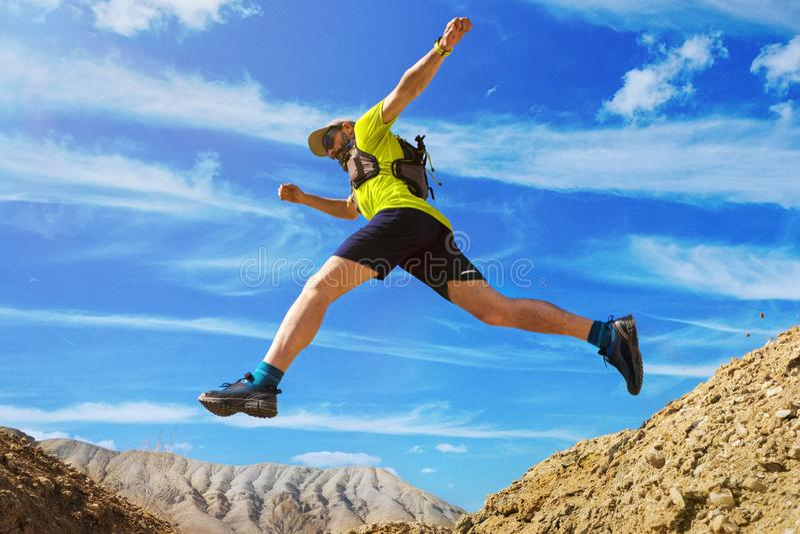 O atleta corre fora de estrada Saltos sobre uma ravina Corredor da fuga no deserto fotografia de stock