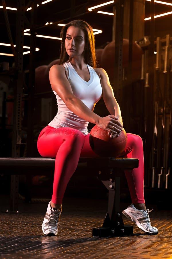 O atleta da jovem mulher está descansando no banco após os exercícios com a bola no gym fotografia de stock