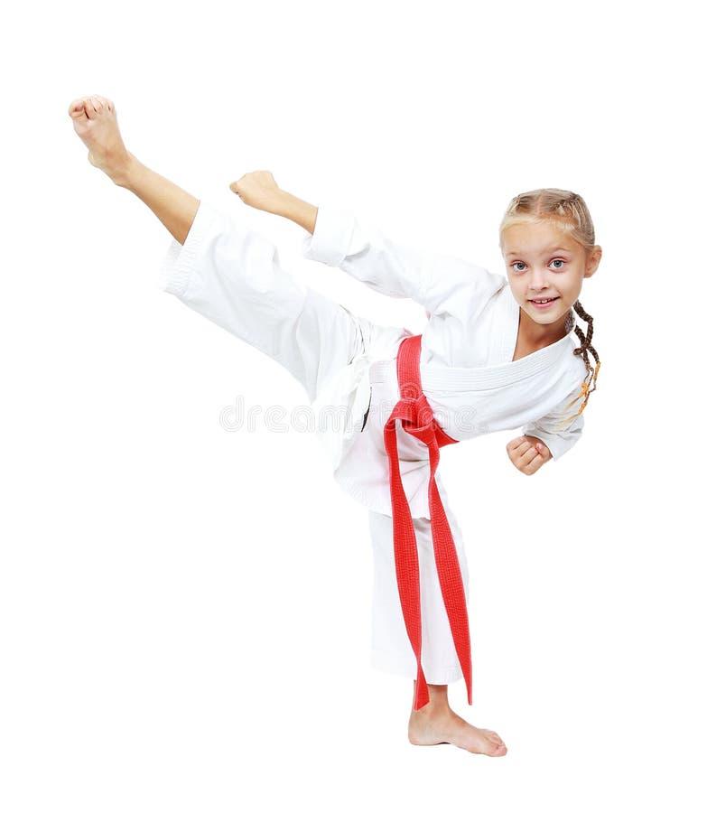 O atleta da menina em um quimono executa uma circular do pontapé isolada fotos de stock royalty free