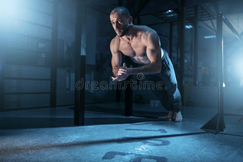 O atleta do músculo faz exercícios das flexões de braço no gym imagens de stock royalty free