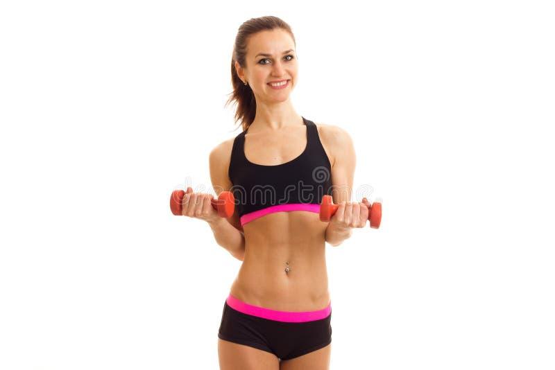 O atleta fêmea de sorriso dos jovens está na frente da câmera na parte superior e no short e em guardar um peso imagens de stock