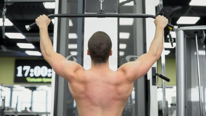 O atleta faz exercícios para os músculos da parte traseira Parte traseira muscular do halterofilista no dispositivo de bloco no g fotografia de stock royalty free