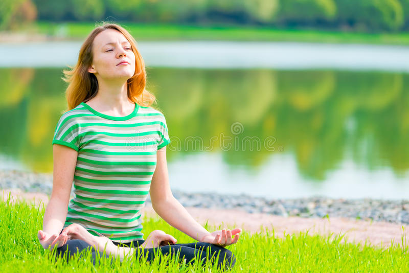 O atleta focalizado relaxa em uma posição de lótus fotos de stock royalty free