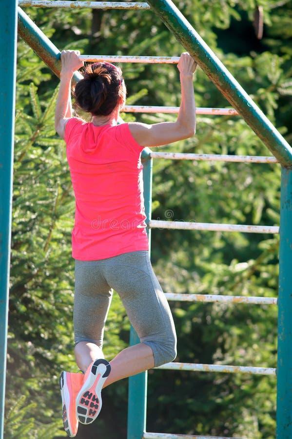 O atleta forte da mulher é Chin-UPS e Pullups que treina em um outd imagem de stock royalty free