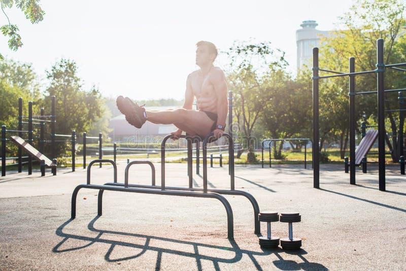 O atleta forte novo que dá certo no gym exterior, fazendo o Abs de levantamento do pé exercita foto de stock royalty free