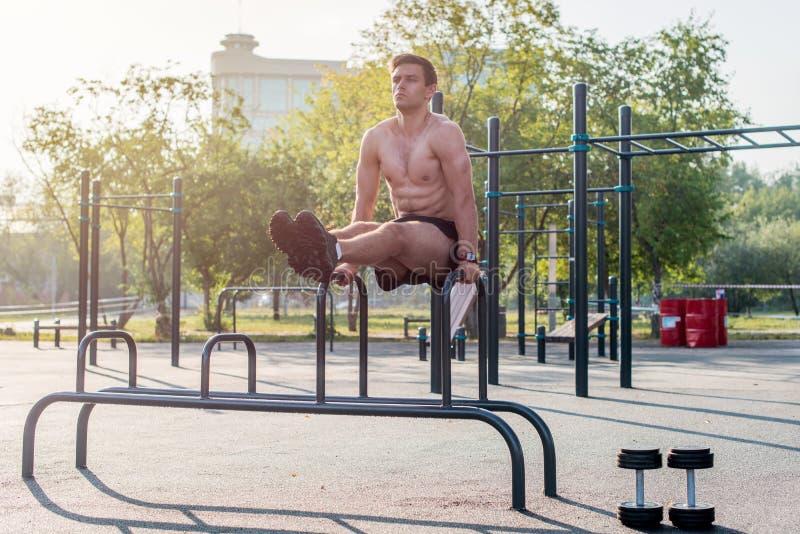 O atleta forte novo que dá certo no gym exterior, fazendo o Abs de levantamento do pé exercita imagens de stock