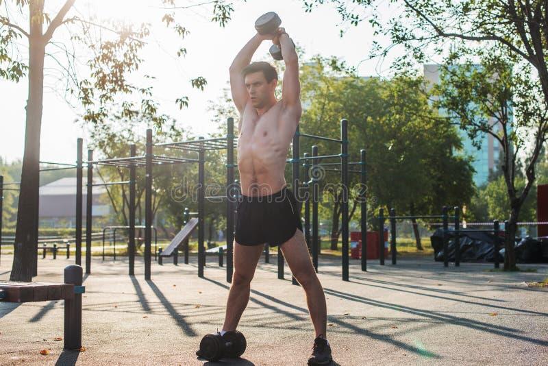 O atleta masculino muscular com braços levantou fazer pesos de levantamento dos exercícios imagem de stock