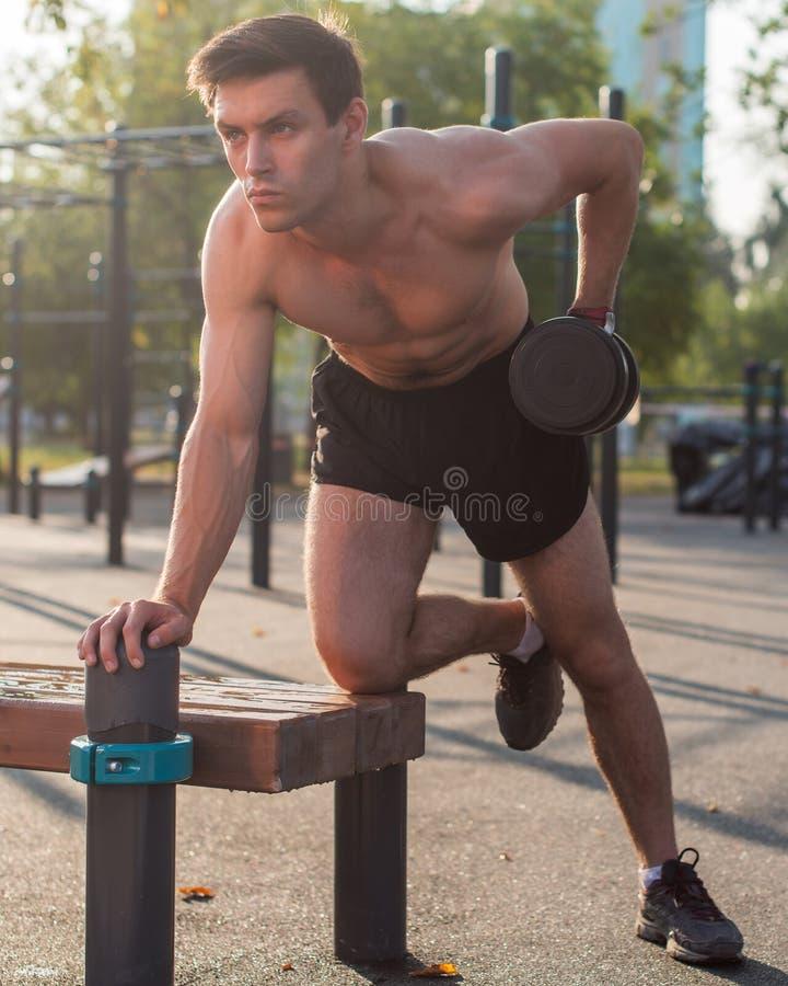 O atleta masculino muscular com braços levantou fazer pesos de levantamento dos exercícios foto de stock royalty free