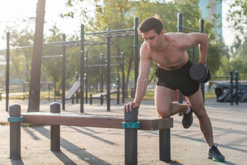 O atleta masculino muscular com braços levantou fazer pesos de levantamento dos exercícios imagens de stock royalty free
