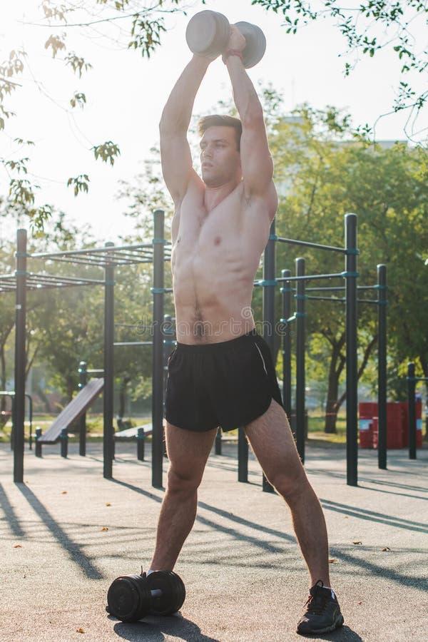 O atleta masculino muscular com braços levantou fazer pesos de levantamento dos exercícios fotos de stock royalty free