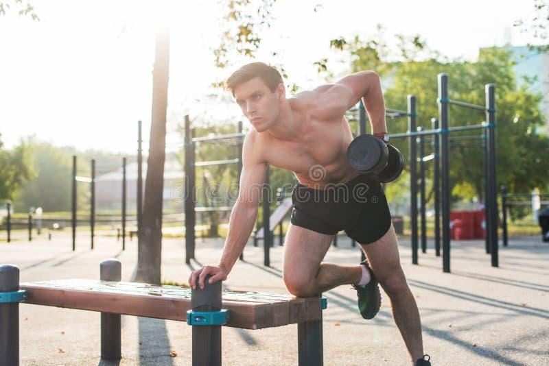 O atleta masculino muscular com braços levantou fazer pesos de levantamento dos exercícios foto de stock
