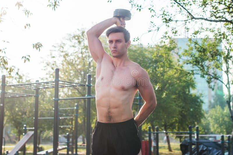 O atleta masculino muscular com braços levantou fazer pesos de levantamento dos exercícios fotografia de stock royalty free