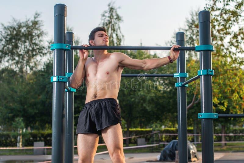 O atleta masculino novo que faz o queixo-acima exercita no parque Homem da aptidão que dá certo fora fotos de stock
