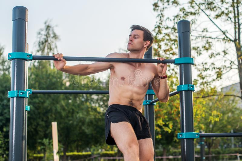 O atleta masculino novo que faz o queixo-acima exercita no parque Homem da aptidão que dá certo fora imagens de stock royalty free