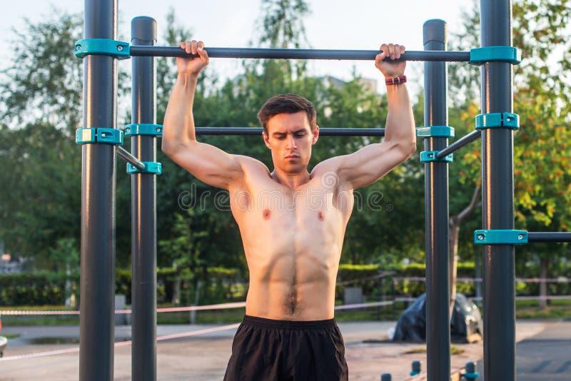 O atleta masculino novo que faz o queixo-acima exercita no parque Homem da aptidão que dá certo fora imagens de stock