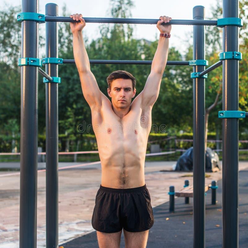 O atleta masculino novo que faz o queixo-acima exercita no parque Homem da aptidão que dá certo fora imagem de stock royalty free