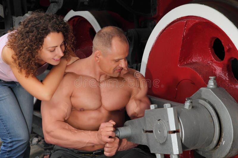 O atleta, a mulher nova e o `s da locomotiva rodam imagens de stock