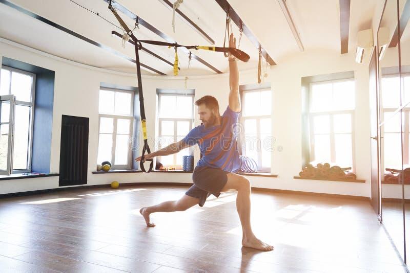 O atleta muscular considerável do homem que faz o exercício apenas com as correias da aptidão no clube moderno do gym, malha o ún fotografia de stock