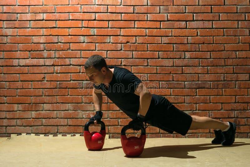O atleta na flexão de braço em pesos, exercício do gym ostenta imagens de stock royalty free