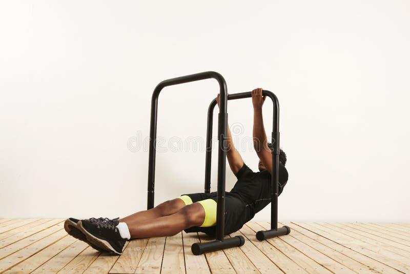 O atleta preto novo que faz o peso do corpo enfileira em barras móveis imagem de stock royalty free