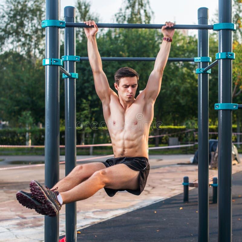 O atleta que pendura na estação da aptidão que executa os pés aumenta Treinamento transversal do núcleo que dá certo os músculos  imagem de stock royalty free