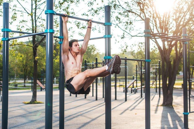 O atleta que pendura na estação da aptidão que executa os pés aumenta Treinamento transversal do núcleo que dá certo os músculos  imagens de stock