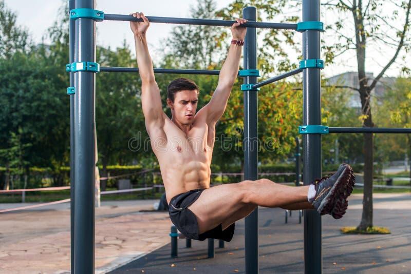 O atleta que pendura na estação da aptidão que executa os pés aumenta Treinamento transversal do núcleo que dá certo os músculos  fotografia de stock royalty free