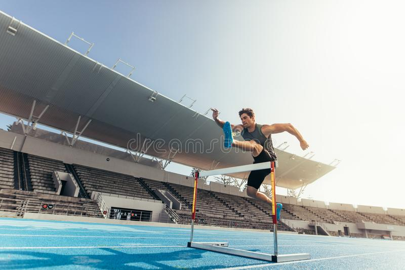 O atleta que salta sobre um obstáculo na pista de atletismo imagens de stock