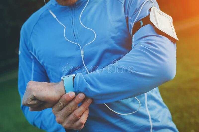 O atleta que verifica o tempo resulta em seu relógio esperto no pulso foto de stock royalty free