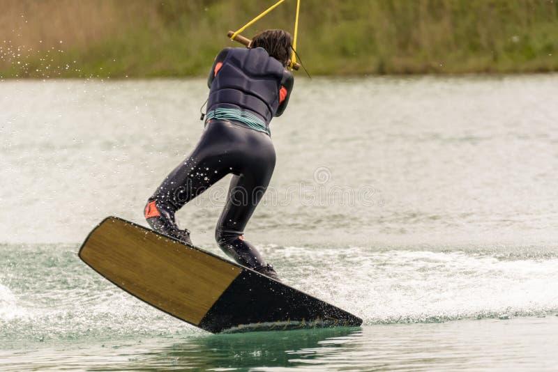 O atleta Woman é Wakeboarding no parque do cabo fotografia de stock royalty free