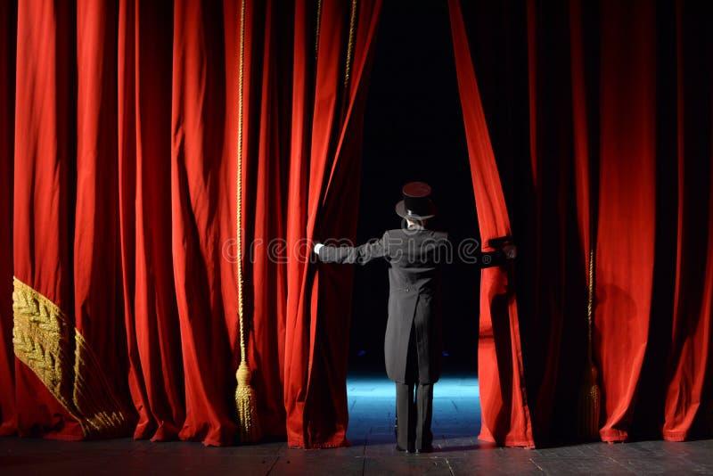 O ator em uma cortina da fase do smoking abre imagens de stock
